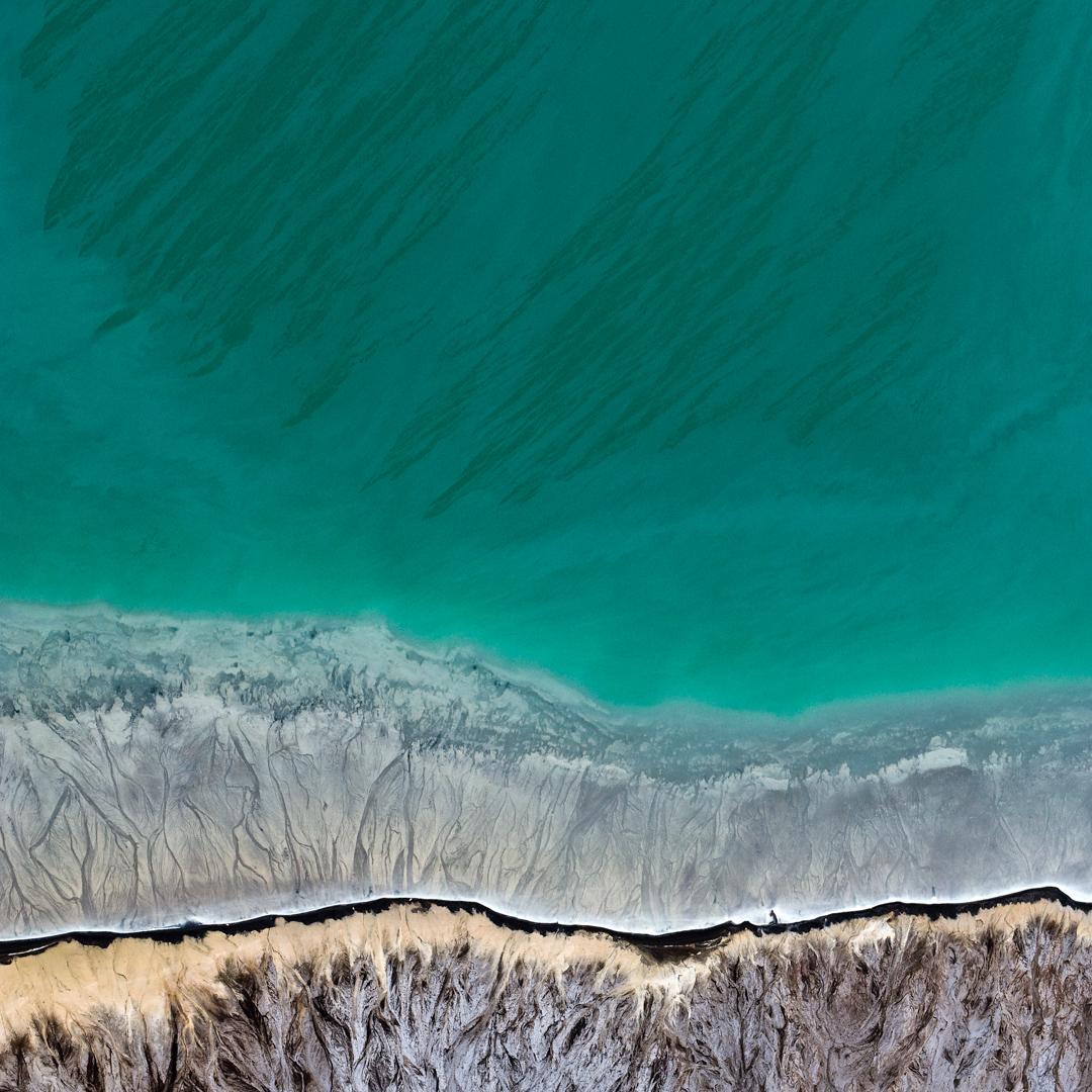 Zdjęcie przedstawia wodę i brzeg na dole zdjęcia. Zdjęcie zrobione jest z góry. Woda przy brzegu jest przejrzysta, zaś tam, gdzie brzeg się kończy woda przybiera kolor turkusowy.