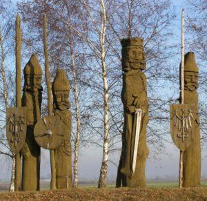 Wysokie drewniane rzeźby przedstawiające króla Bolesława Chrobrego wraz z drużynnikami, stojące w jednym rzędzie.
